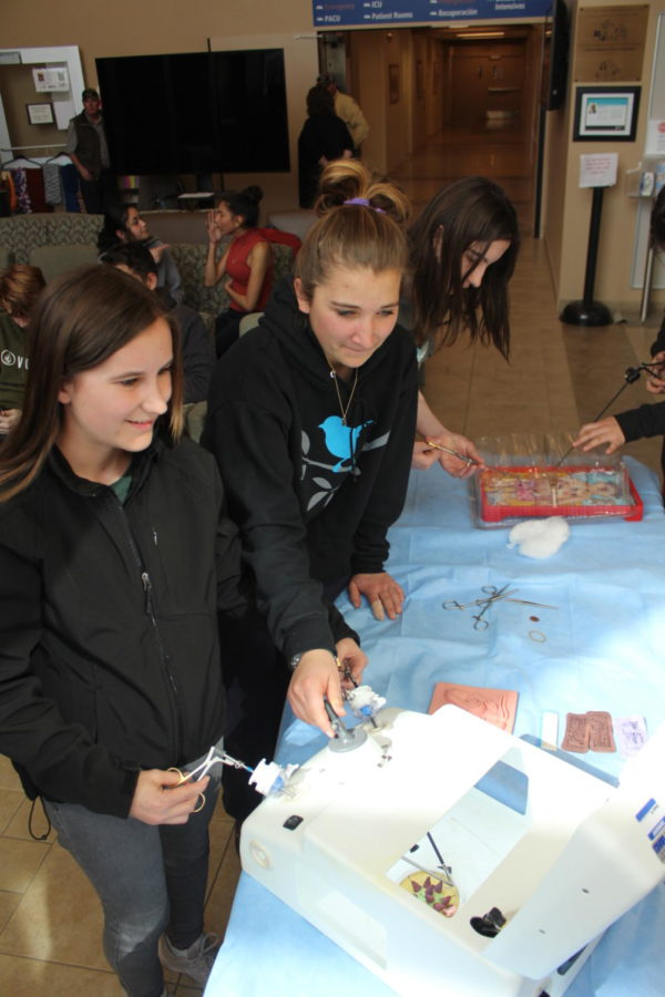Meghan Johnson and Andrea Lee practice threading a needle using laparoscopic tools.