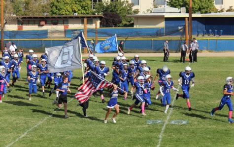 BUHS Jv football team & cheerleaders running out onto the field
